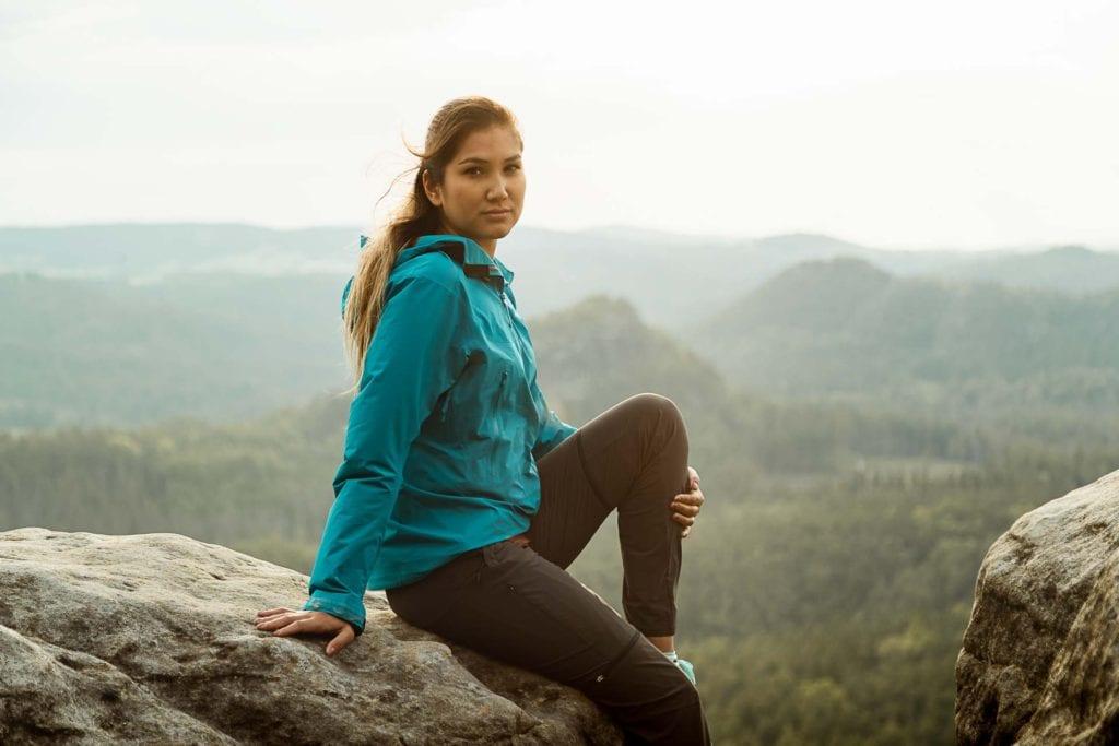 Portrait einer jungen Frau in Outdoor-Klamotte vor der Landschaft der Sächsischen Schweiz. Bettina während der Nahweh-Kampagne von Globetrotter in der Sächsischen Schweiz.