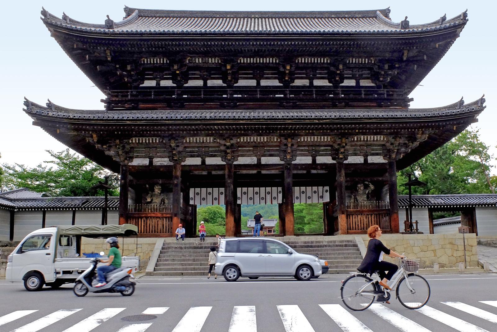 Fahrradfahrerin vor einem Tempel in Kyoto