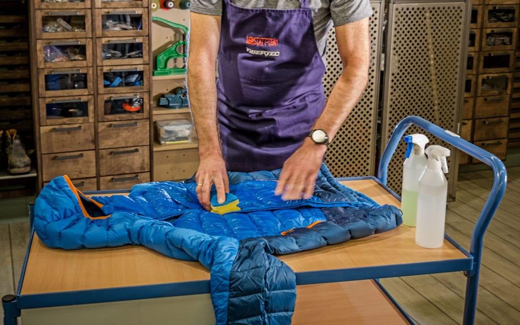 Mann wäscht eine Daunenjacke