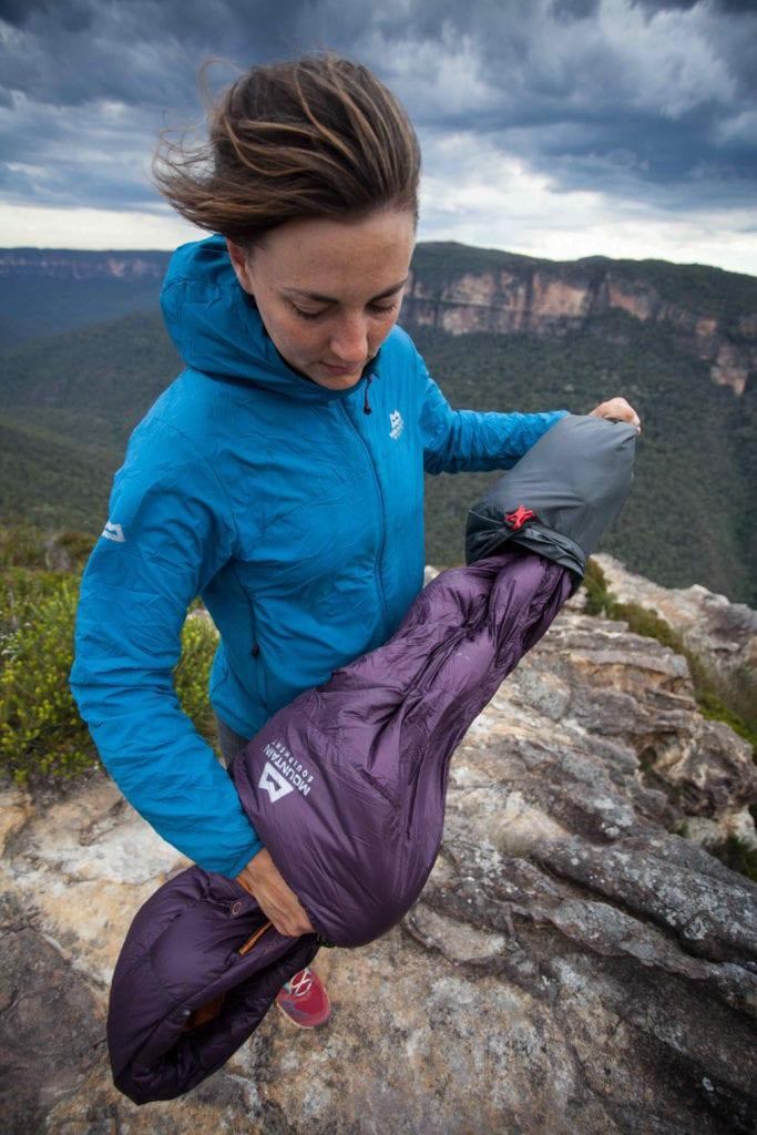 Frau packt Schlafsack aus