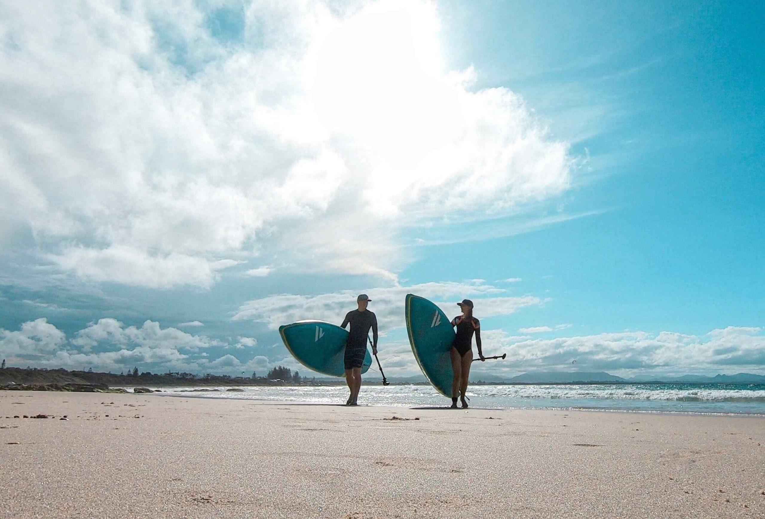 Surfer am Strand der Bryon Bay mit SUPs