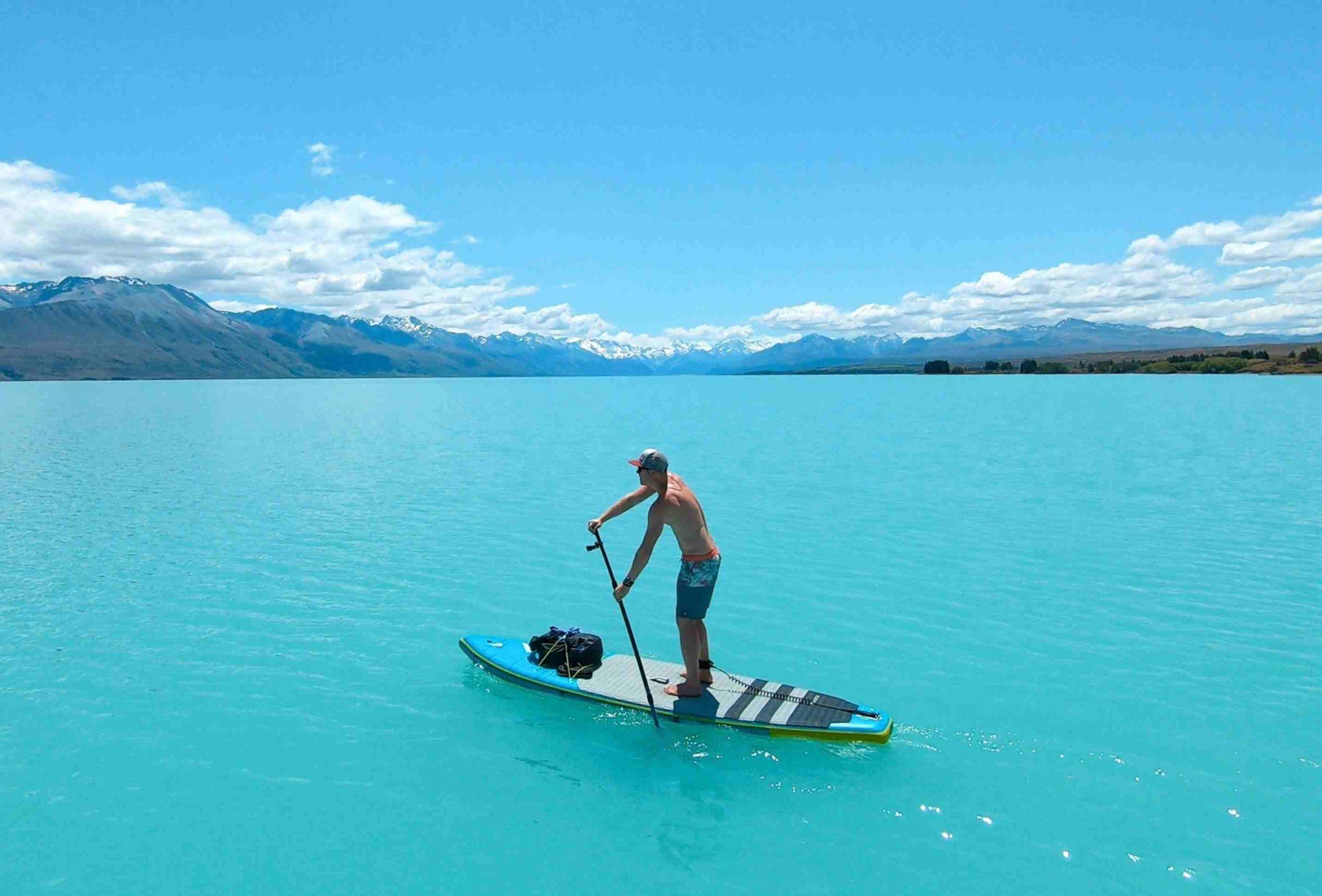 Mann paddelt auf dem SUP auf dem Lake Pukaki