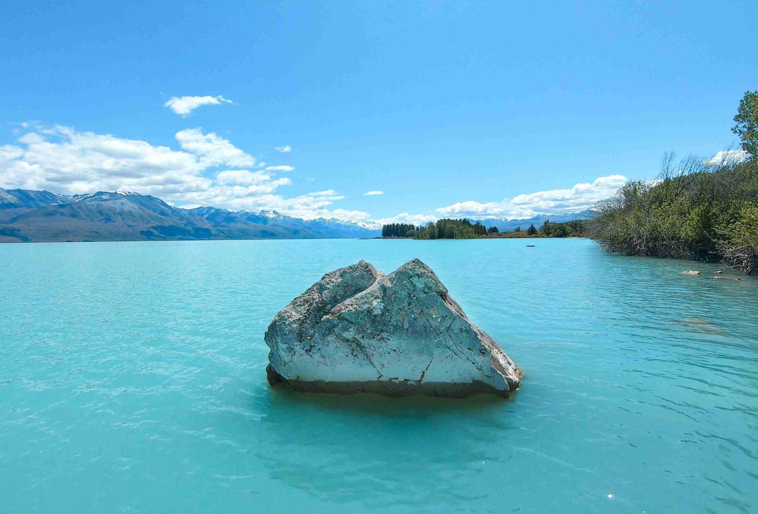 Ein Fels, der aus dem Wasser schaut, in dem See Lake Pukaki