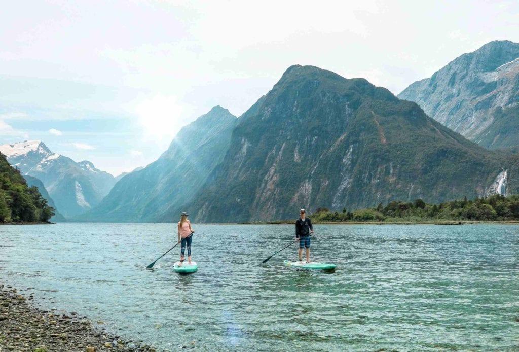 Zwei Personen paddeln mit dem SUP über den Milford Sound