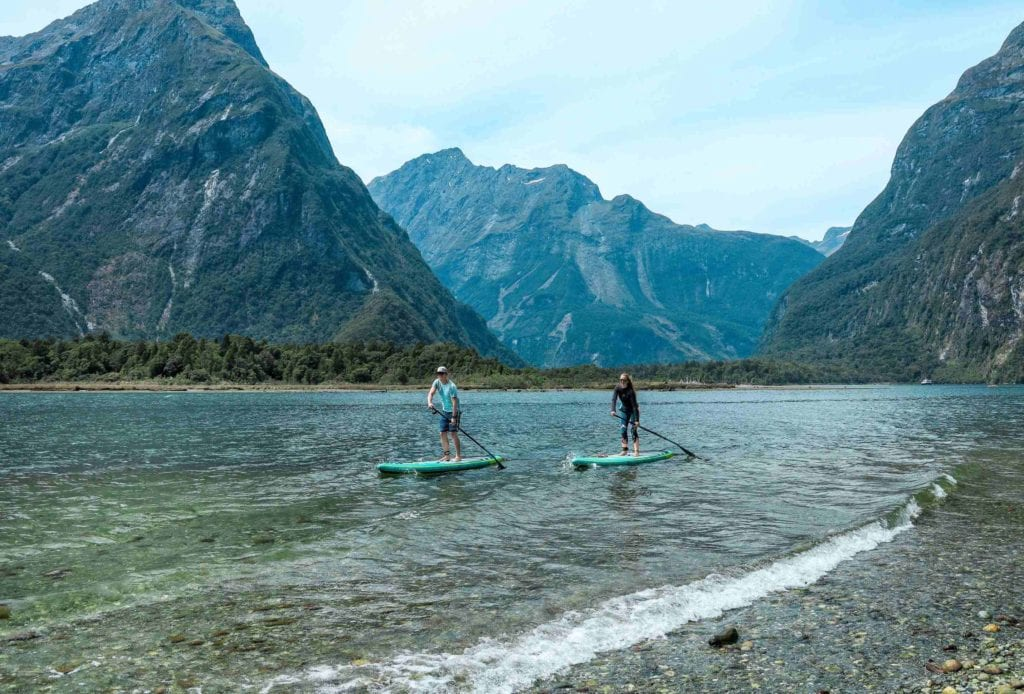 Zwei Personen paddeln auf den SUPs auf dem Milford Sound im Hintergrund Berge