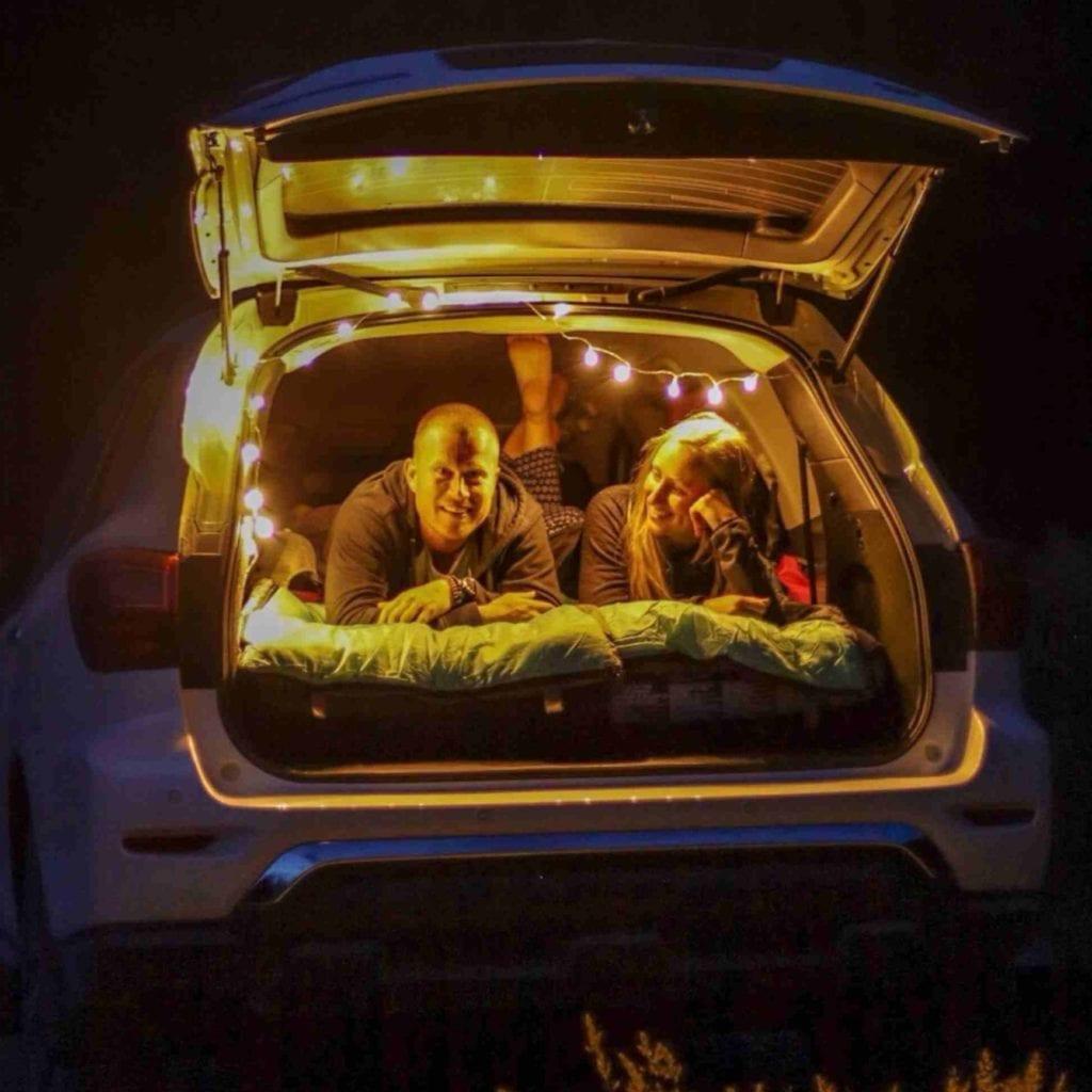 Camping im Kofferraum eines Autos mit einer Lichterkette als Lampe