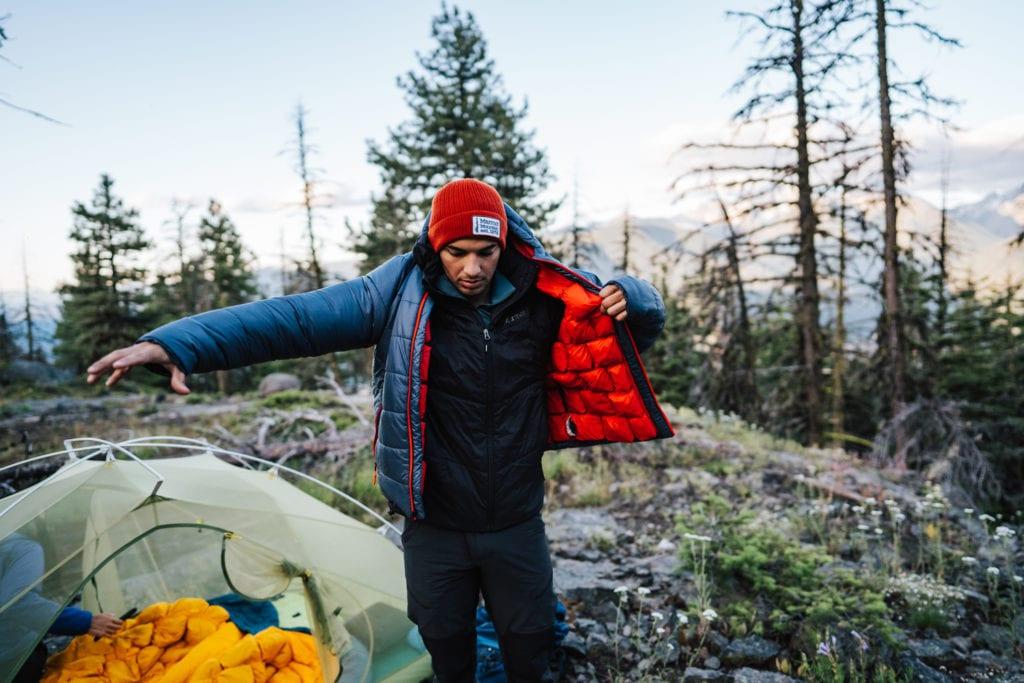 Mann beim Campen zieht sich seine Daunenjacke an.