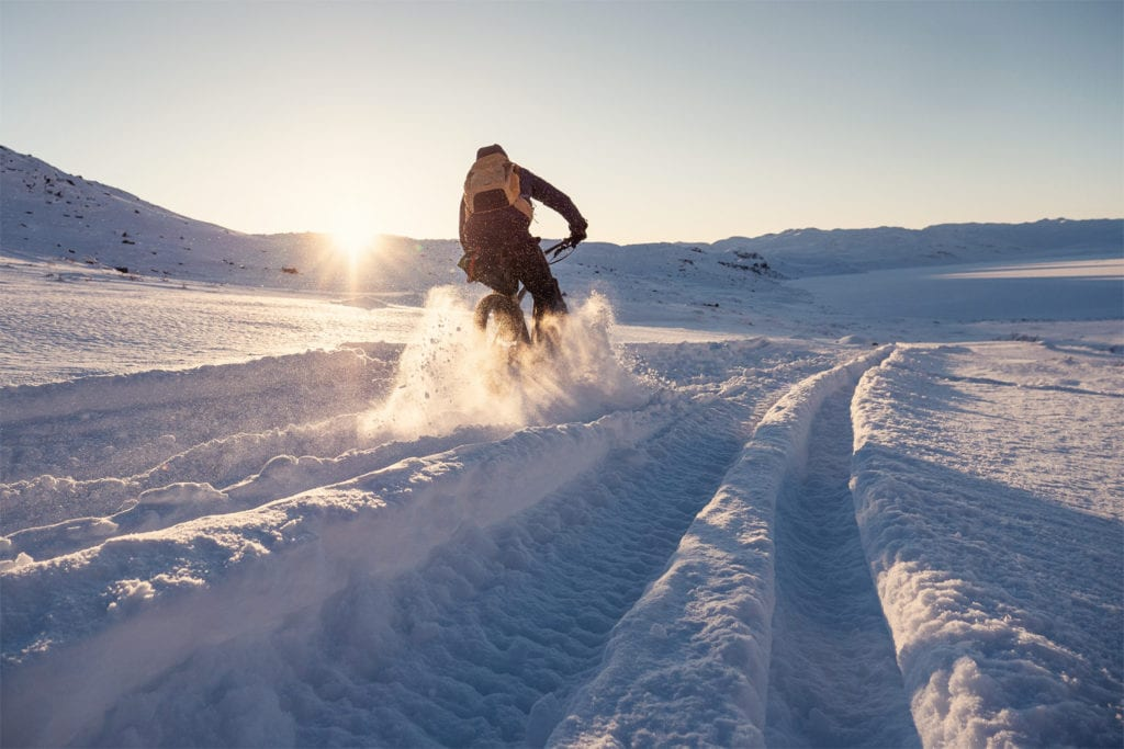 Mountainbiker fährt durch den Schnee in Grönland.