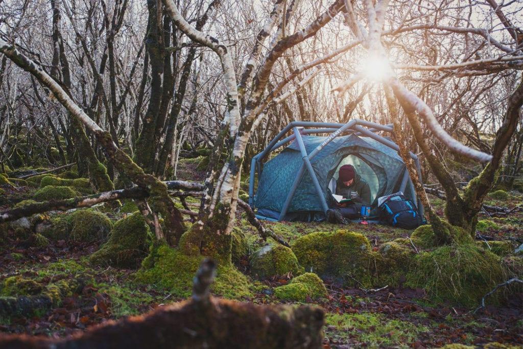 Mann im Zelt im Wald.
