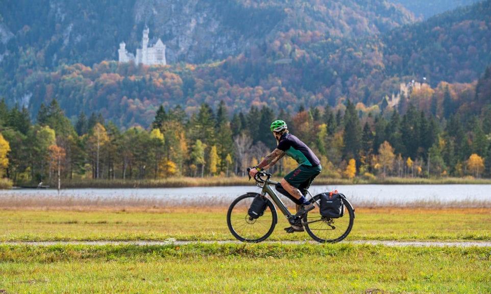 Gravelbiker am Schwansee mit Schloss Neuschwanstein im Hintergrund