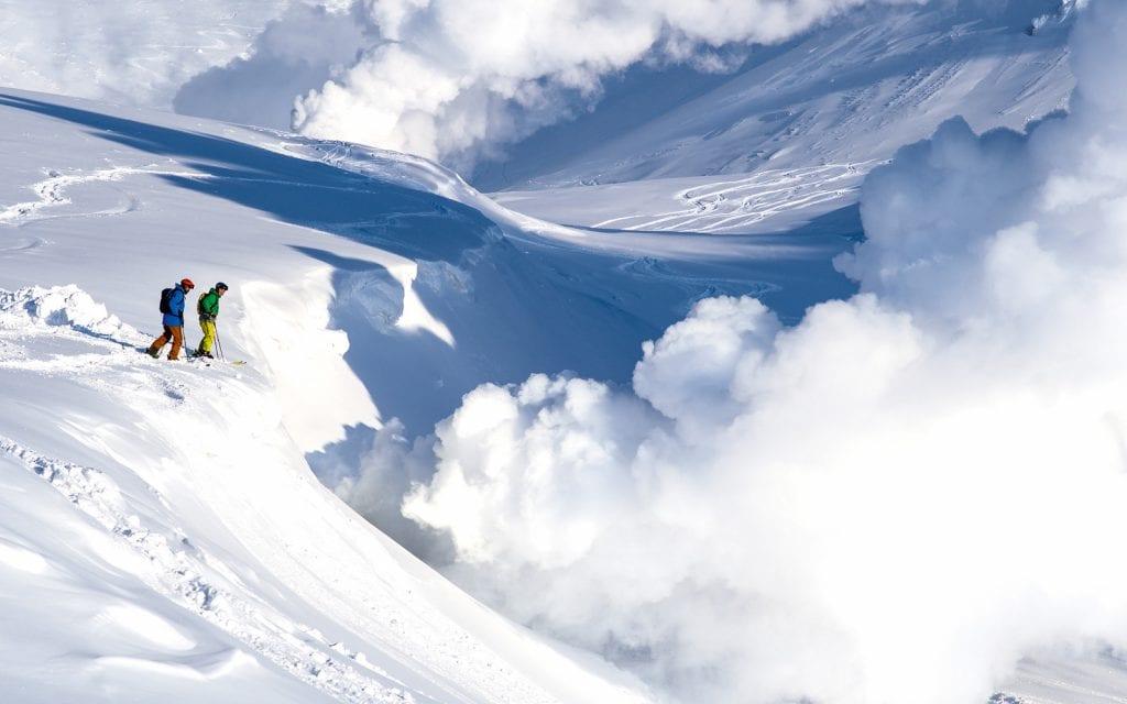 Zwei Skifahrer nähern sich den Fumarolen im Skigebiet Asahidake in Japan.