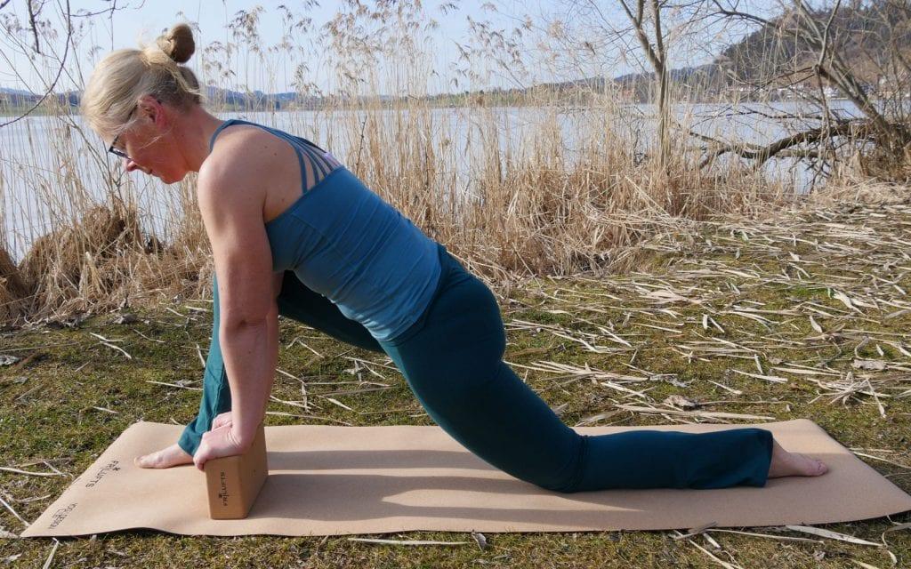 Yoga-Übungen für Anfänger. Drache mit Unterstützung durch einen Yoga-Block.
