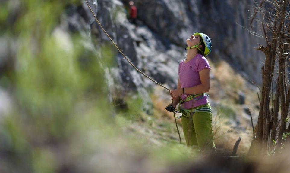 Kletterin sichert einen Vorsteiger.