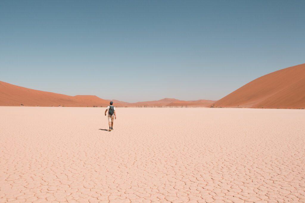 Felix mit Rucksack , läuft Richtung Dünen im Hintergrund