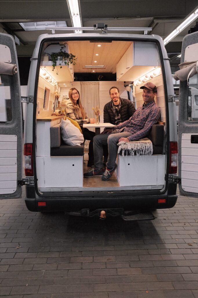 Offener Van in dem Julia und Nando sitzen