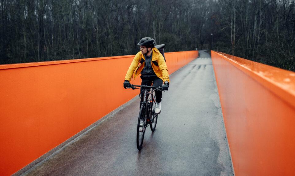 Roeckl-Mann-auf-Fahrrad-auf-orangener-Bruecke
